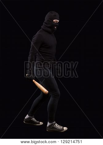 Man in black with black mask on. Burglar going to steak something or someone. Man holding bat over black background. Isolated on black.