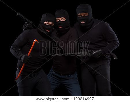 Picture of experienced and dangerous thieves in black masks in studio. Men in black balaclavas posing with crowbar, gun, rifle, etc. Isolated on black.
