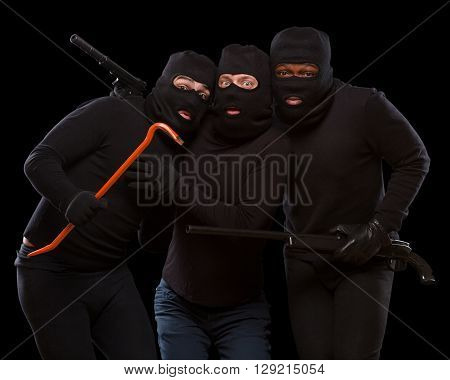Portrait of three gangsters posing with rifle, crowbar and gun in studio. Dangerous people in balaclavas over dark grey background. Isolated on black.