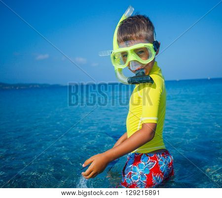 Joyful boy going to scuba diving in clear sea.