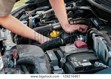 Caucasian man he repairs his car on the indoor