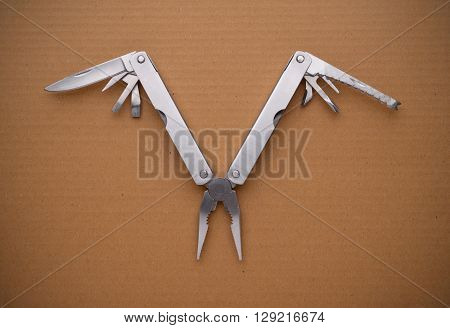 Multitool bird on cardboard. A tool for a variety of cases.