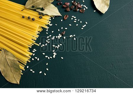 Raw spaghetti and Bay leaf, barberry, pepper, sesame seeds on black-blue-green wooden background, top view place for text
