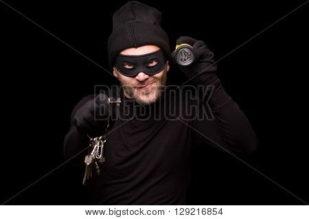 Portrait of masked thief holding flashlight and keys. Handsome man looking at camera over black background. Isolated on black.