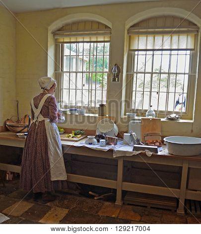 Saffron Walden, Essex, England - May 07, 2016: Victorian Kitchen maid preparing food by window.