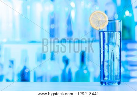 One glass of crystal water decorated with lemon slice at the blue bar lighting