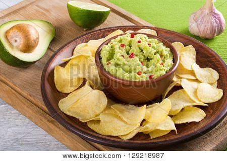 bowl of guacamole dip and potato chips on a clay brown dish on a green table mat with slice of lime on a white wooden background view from above