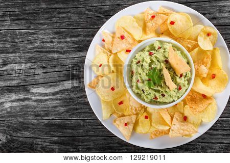bowl of guacamole dip and potato chips on a white dish on a wooden background view from above