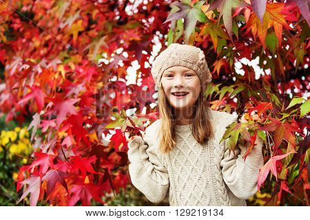 Autumn portrait of a cute little girl of 7-8 years old