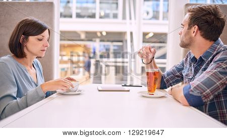 Caucasian male and female couple having relationship issues. They are not even able to make eye contact with one and other, as both of the put off initiating conversation.