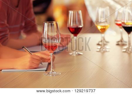 Woman tasting new sorts of wine at the table