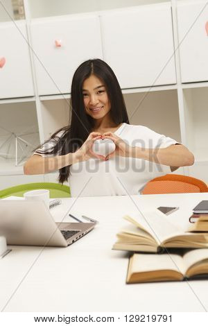 Asian student showing heart to camera while sitting in library and preparing for lessons, classes or exams. Happy brunette studying.