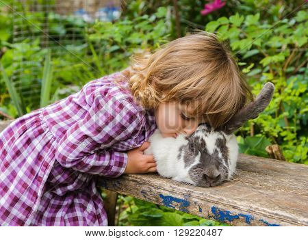 Little girl hugging a large spotted rabbit