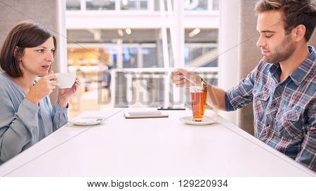 Woman pulls her face funny as she looks at her male partner while he removes his tea bag from his tea. She apperas to be irritated with his behaviour, evident from the status of their relationship
