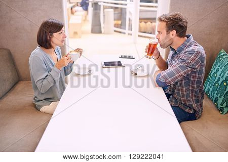 White man and woman having drinks together in a modern coffee shop. There is a tablet and a phone on the table between them, as well as a slight awkwardness amongst them