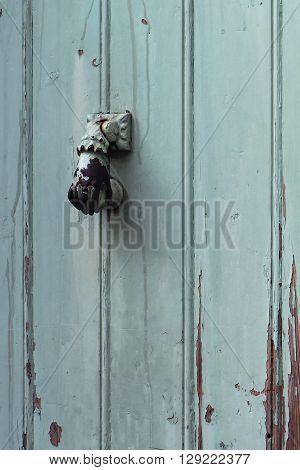 Old metal door knocker on wood door surface