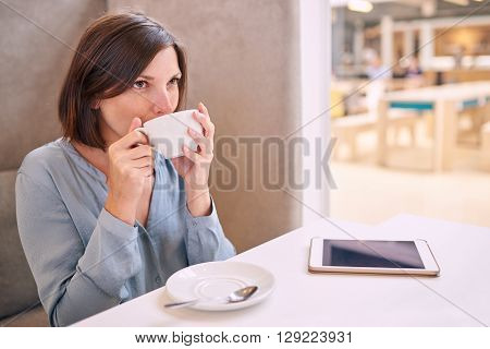 well dressed professional caucasian woman taking a sip of her coffee while sitting in a bright cafe with her tablet on the table infront of her.