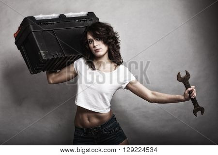 Sex equality and feminism. Sexy girl holding toolbox and wrench spanner tool. Attractive woman working as repairman or mechanic