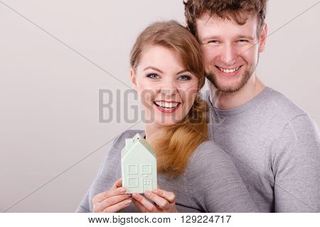 Cheerful Young Couple With House Model.