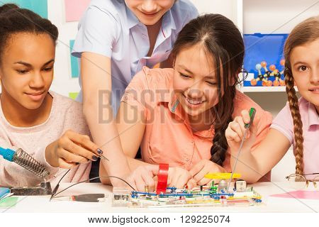 Four smiling pupils learning physics, assembling electric chain with electronic constructor