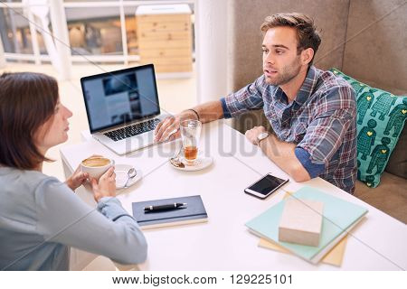 Man busy making a business presentation to a well know successful mature business woman who might be his future investor if everything goes well.