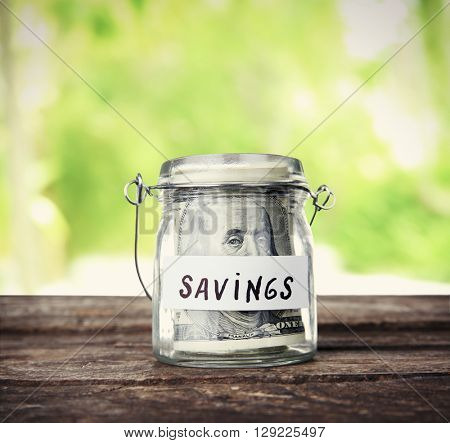 Jar for savings full of coins on nature background
