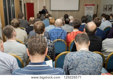 Attentive listeners look at stage at business conference