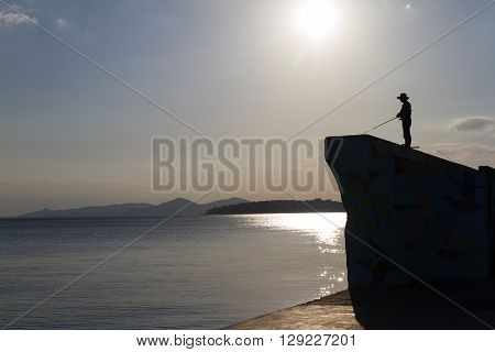 Silhouette Of Fisheman With Fishing-rod In Afternoon Light