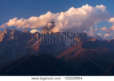 Mountain top in clouds. Beautiful sunset. Mount Ushba. Caucasus, Georgia, Zemo Svaneti