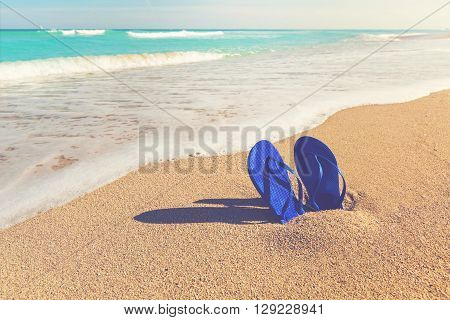 Sandals Stuck In The Sand Of A Tropical Beach