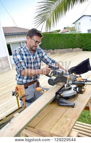 Carpenter cutting planks for wooden deck