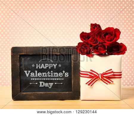 Valentines message on a small chalkboard with red roses