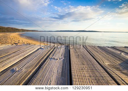 Summer At The Beach. Wooden dock overlooks a sunny sandy beach with a blue water horizon.
