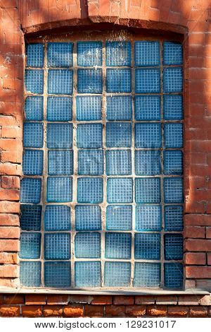 The old broken glass block windows in the brick wall. Background for design. Texture