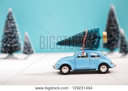 Car Carrying A Christmas Tree In Miniature Evergreen Forest