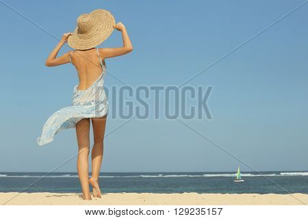 Girl on the beach looking at the hoizon