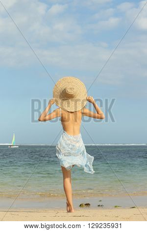 Girl on the beach with big straw hat