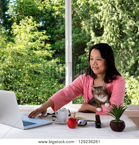 Mature woman wearing morning attire holding her family pet cat while working from home in front of large window with bright daylight and trees in background.