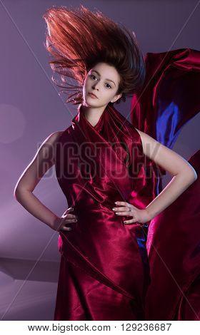 Studio shoot of young woman wrapped in maroon fabric, freezing mode photography