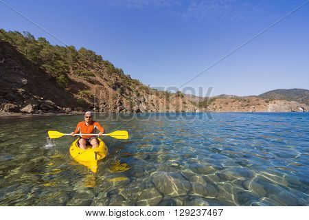 Men travel by canoe on the sea in the summer.