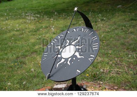 Modern blackand white sun dial in a garden
