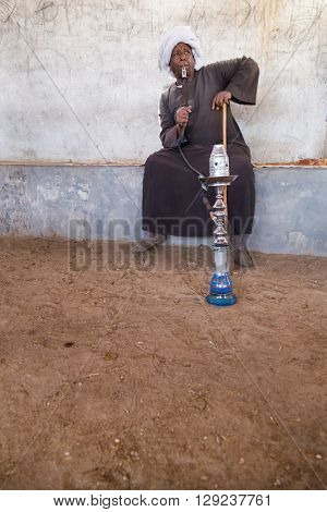DARAW, EGYPT - FEBRUARY 6, 2016: Local camel salesman smoking shisha pipe.