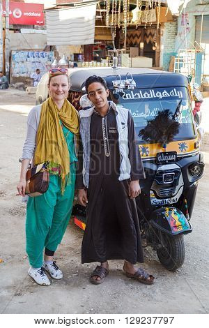 DARAW, EGYPT - FEBRUARY 6, 2016: Tourist posing with the driver of Tuk-tuk vehicle on the street.