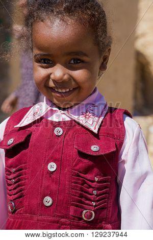 ASWAN, EGYPT - FEBRUARY 7, 2016: Portrait of cute local girl on street of Nubian village on the Nile.