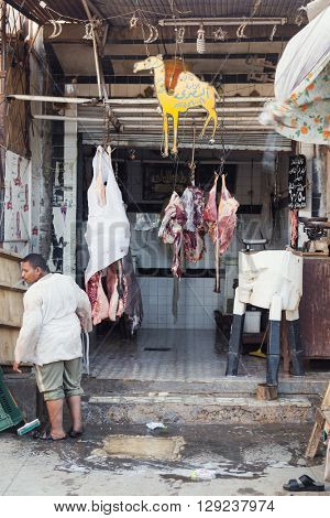 DARAW, EGYPT - FEBRUARY 6, 2016: Local butcher spitting in front of the shop.