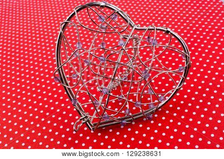 Heart cage made of metal wire on a red background