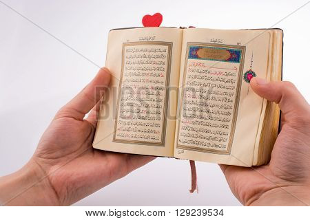 Hand holding The Holy Quran with a heart on a white background