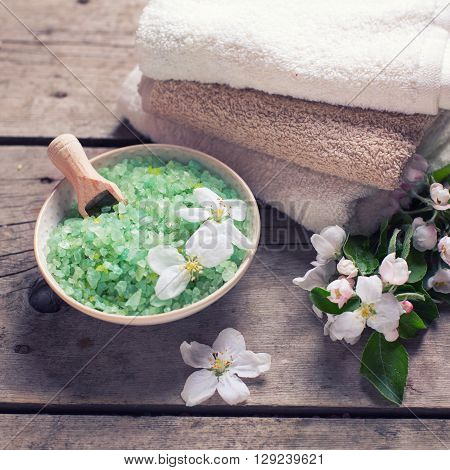 Spa or wellness organic product. Green sea salt in bowl towels and flowers on aged wooden background. Selective focus. Place for text. Square image.