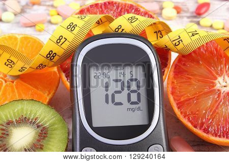 Glucometer with result of measurement sugar level tape measure fresh fruits and medical tablets or supplements concept of diabetes slimming and healthy lifestyle