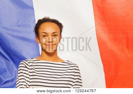 Portrait of beautiful African teenage girl in frock with French flag on background